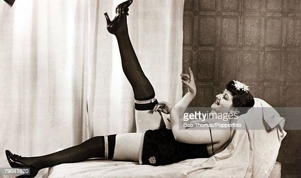 Erotic Postcard circa 1920 Dishabille Mature dark haired woman in her underwear and hold up stockings with one leg in the air