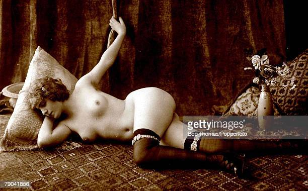 Erotic Postcard circa 1920 Dishabille Nude Naked woman save for garters and stockings lying full length in a studio setting