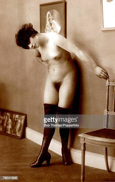 Erotic Postcard circa 1920 Dishabille Nude Naked woman save for boots and stockings posing standing by a wall