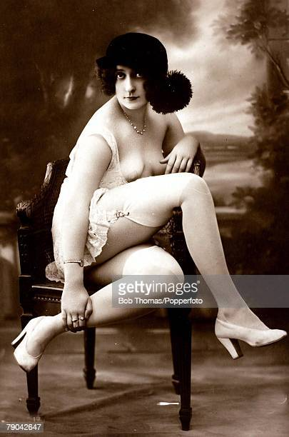 Erotic Postcard circa 1920 Dishabille Partly clad dark haired woman serious wearing stockings and suspenders