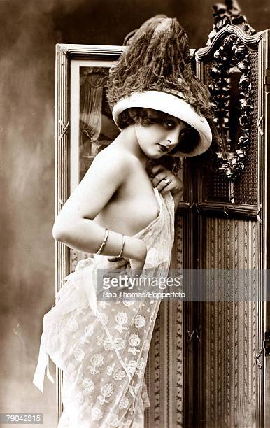 Erotic Postcard circa 1920 Dishabille Young dark haired woman wearing lacy negligee and an extravagant hat