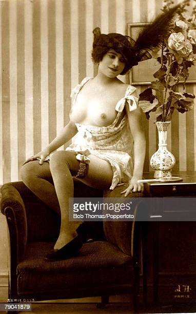 Erotic Postcard circa 1920 Dishabille Young dark woman wearing hat with large feather topless posing on a chair