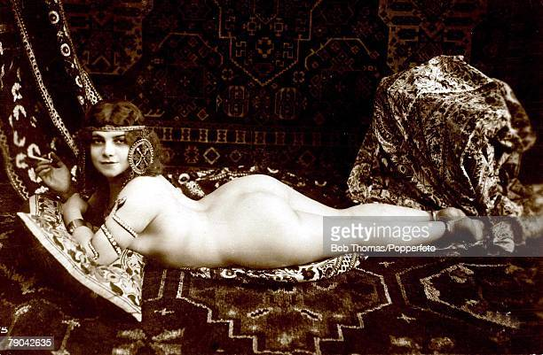 Erotic Postcard circa 1920Nude Naked woman smoking a cigarette lying on her stomach on a large rug