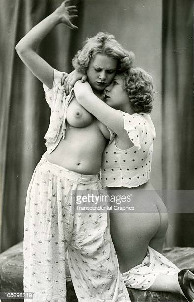 Erotic postcard features a photograph of a topless young woman apparently poised to spank the bare buttocks of another young woman who embraces her...