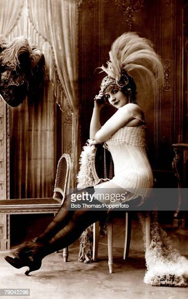 Erotic Postcard France circa 1920 Dark haired woman wearing underwear stockings and suspenders and a feathered head dress