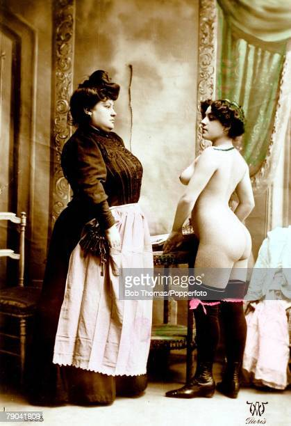 Erotic Postcard France circa 1920 Dark haired young woman and madame in a scene from a brothel