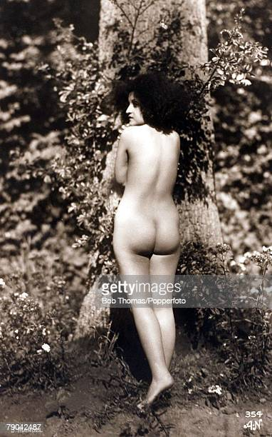 Erotic Postcards, Circa 1915, A picture of a nude woman standing with her back towards the camera near some foliage within a forest location