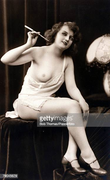 Erotic Postcards Circa 1915 Dishabille Dark haired woman wearing an undergarment pulled down to expose her breast whilst holding a cigarette in a...