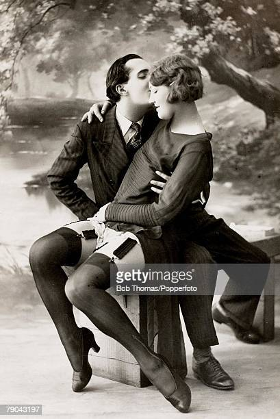 Erotic Postcards Circa 1920 Dishabille A picture of a man who is gently kissing a woman who is wearing suspenders whilst sitting on his lap