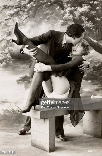 Erotic Postcards Circa 1920 Dishabille A picture of a smartly dressed man who is holding and also kissing a woman who sits on a bench with her legs...