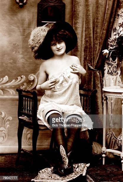 Erotic Postcards Circa 1920 Dishabille A picture of a woman sitting on a couch wearing underwear and a large hat posing for the camera
