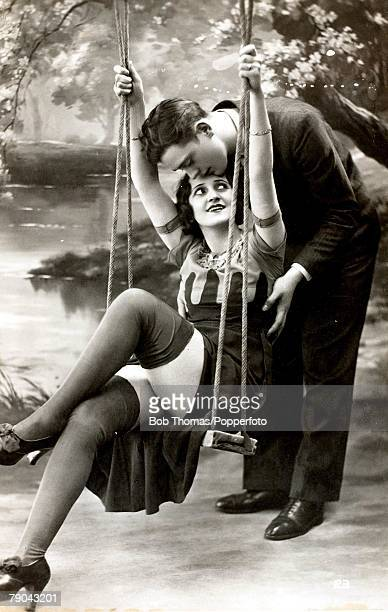Erotic Postcards Circa 1920 Dishabille A picture of a woman sitting on a swing with her legs crossed whilst a man stands holding her gently from...