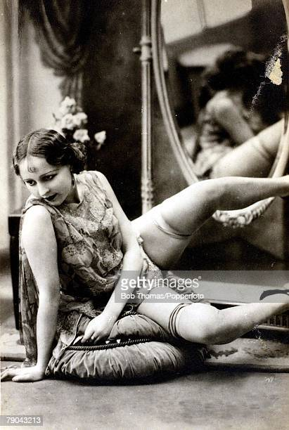 Erotic Postcards Circa 1920 Dishabille A picture of a woman wearing a skimpy dress sitting down with her legs in the air posing for the camera