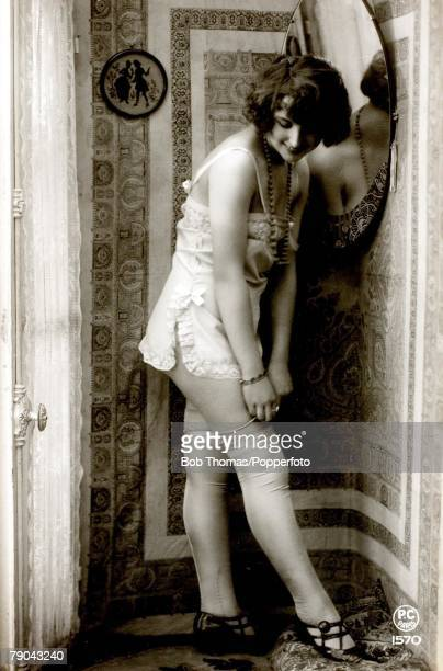 Erotic Postcards Circa 1920 Dishabille A picture of a woman wearing a skimpy night dress standing near a mirror whilst posing for the camera