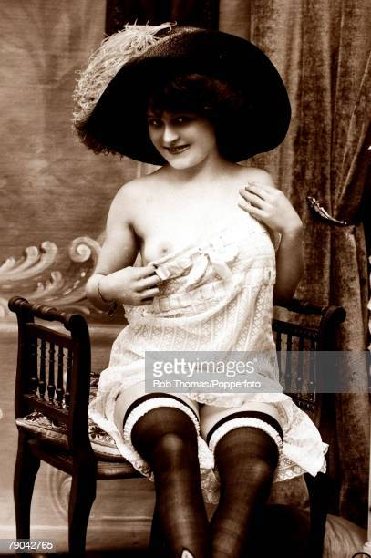 Erotic Postcards Circa 1920 Dishabille A picture of a woman wearing underwear and a large hat posing for the camera whilst revealing a breast