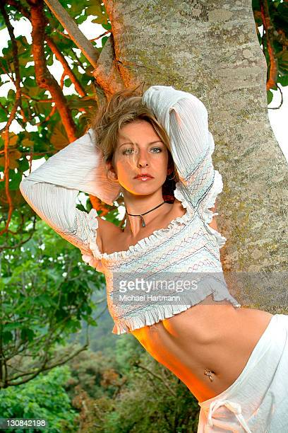 erotic young woman wearing white skirt and top standing under a tree in a garden - under skirt stock photos and pictures