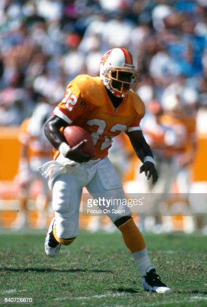 Errict Rhett of the Tampa Bay Buccaneers carries the ball during an NFL football game circa 1995 at Tampa Stadium in Tampa Bay Florida Rhett played...
