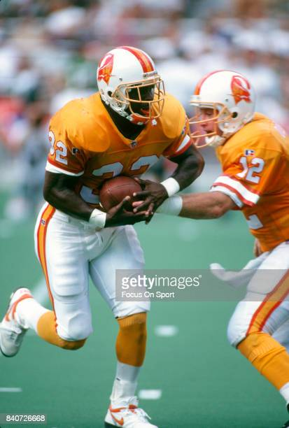 Errict Rhett of the Tampa Bay Buccaneers takes the handoff from quarterback Trent Dilfer against the Philadelphia Eagles during an NFL football game...