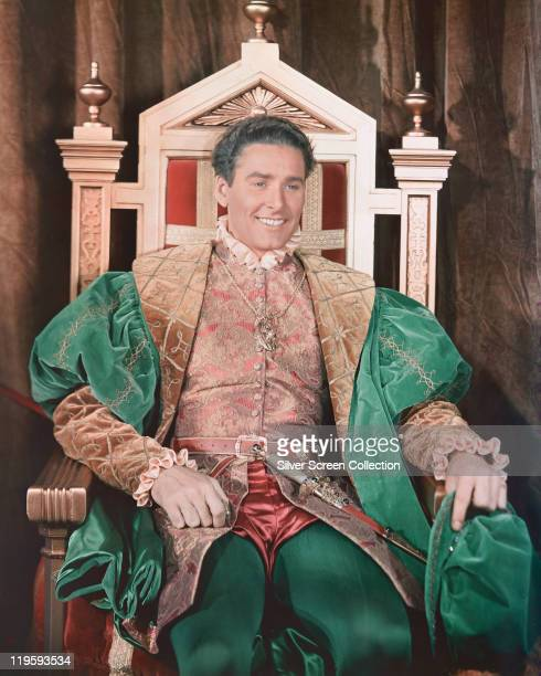 Errol Flynn Australian actor in costume sitting on an ornate chair in a publicity portrait issued for the film 'The Private Lives of Elizabeth and...