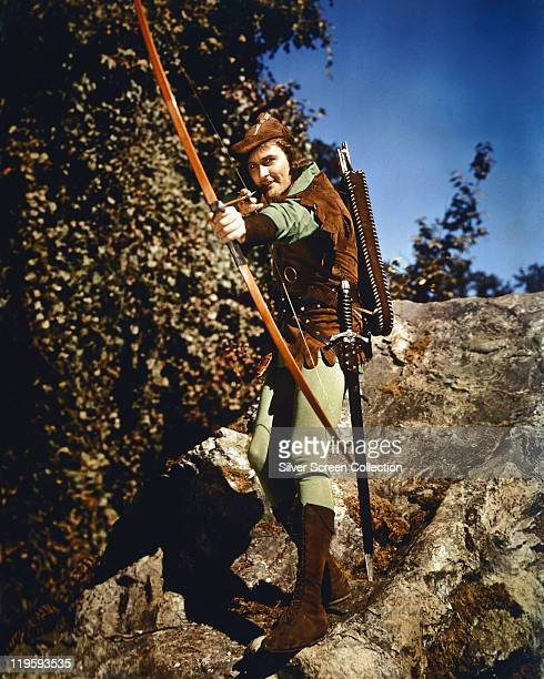 Errol Flynn Australian actor poses in costume taking aim with a bowandarrow in a publicity portrait issued for the film 'The Adventures of Robin...