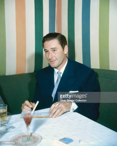 Errol Flynn Australian actor sitting on a green seat and sitting at a table on which drinks rest with striped wallpaper in the background 1950
