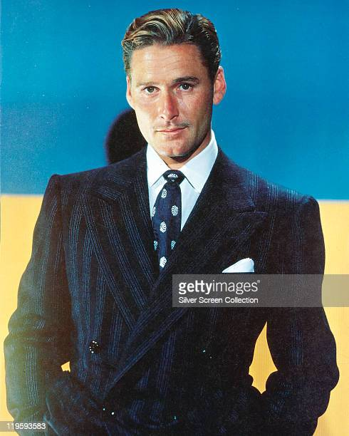 Errol Flynn Australian actor wearing a dark blue jacket white shirt and blue tie with white motifs in a studio portrait with a blue background circa...