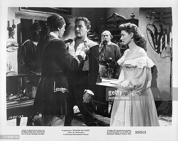 Errol Flynn is grabbed by unidentified actor while Maureen O'Hara watches in a scene from the film 'Against All Flags' 1952