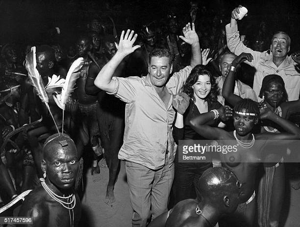 Errol Flynn Juliet Greco and John Huston happily join a group of African dancers All three are on location in Africa working on the 1958 film The...