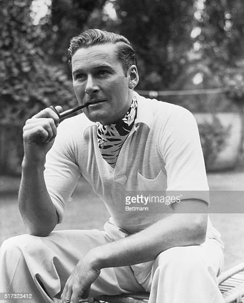 Errol Flynn seated smoking pipe Undated Photo