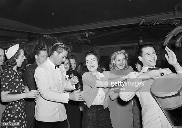 Errol Flynn who has little difficulty performing amazing acrobatic feats before Hollywood cameras seems a little confused as he goes through a Rhumba...