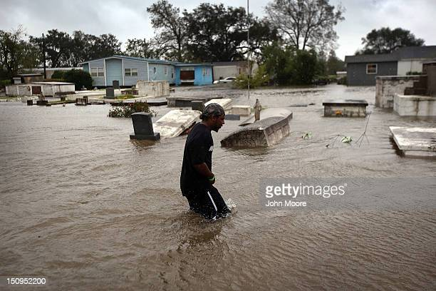 Errol Ragas walks past a cemetery to recover dry blankets from his home as rising waters from Hurricane Isaac flood his neighborhood on August 29...