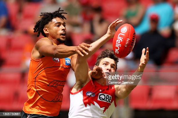 ErrolGulden of the Swans and ConnorIdun of the Giants contest the ball during the AFL Community Series match between the Sydney Swans and the Gold...