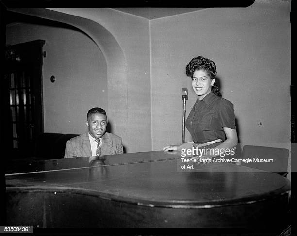 Erroll Garner at piano with woman standing beside him in interior with microphone in background Pittsburgh Pennsylvania 1943