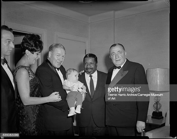 Erroll Garner with three men including one holding baby and woman in interior Pittsburgh Pennsylvania 1960