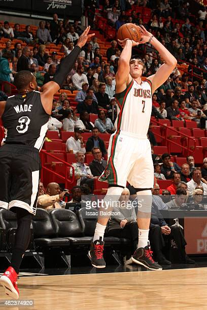 Ersan Ilyasova of the Milwaukee Bucks shoots against Dwyane Wade of the Miami Heat on January 27 2015 at American Airlines Arena in Miami Florida...