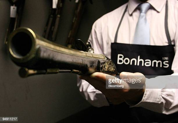 Erskine Berry a cataloguer in the sporting guns department of Bonhams auctioneers in Knightsbridge London displays an 18th century English brass...