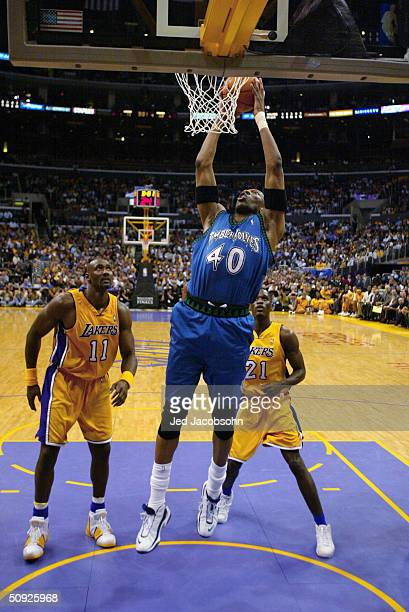 Ervin Johnson of the Minnesota Timberwolves dunks in front of Karl Malone and Kareem Rush of the Los Angeles Lakers in Game three of the Western...