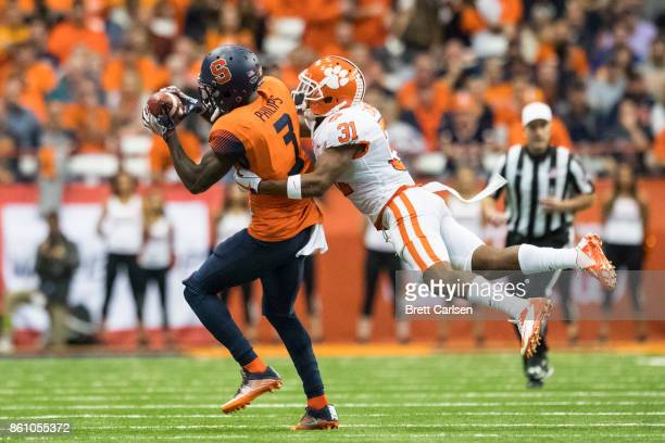 Ervin Philips of the Syracuse Orange makes a first down reception during the second quarter as he is tackled by Ryan Carter of the Clemson Tigers at...