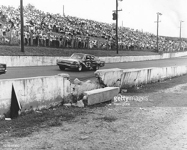Ervin Pruitt drives his Dodge Charger past the area where Earl Brooks had crashed earlier in the Western North Carolina 500 NASCAR Cup race at...