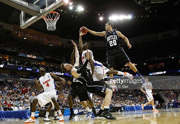 Erving Walker of the Florida Gators fouls Matt Howard as Chrishawn Hopkins of the Butler Bulldogs tries to block his shot in the second half during...