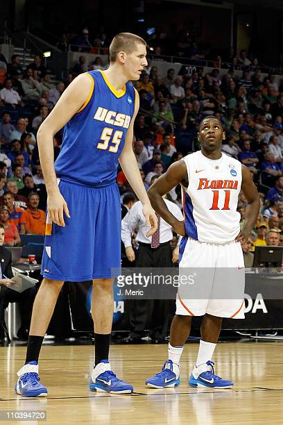 Erving Walker of the Florida Gators looks up at Greg Somogyi of the UC Santa Barbara Gauchos during the second round of the 2011 NCAA men's...