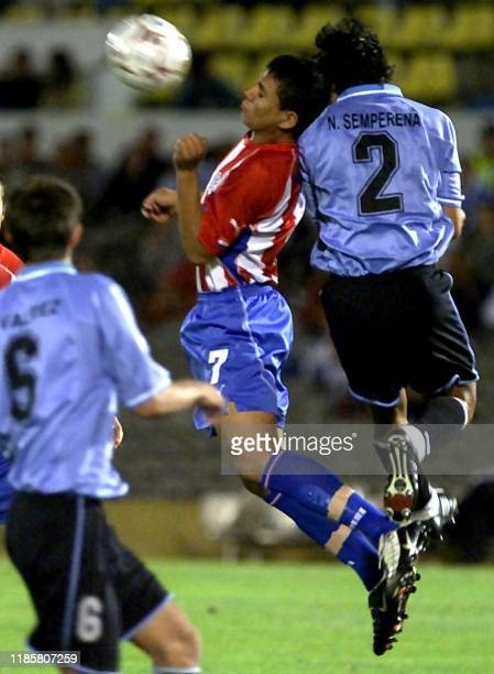 Erwin Avalos from Paraguays soccer team battles over the ball with Nelson Semperana from Uruguay and Carlos Valdez Anthony Silva 19 January 2003 in...