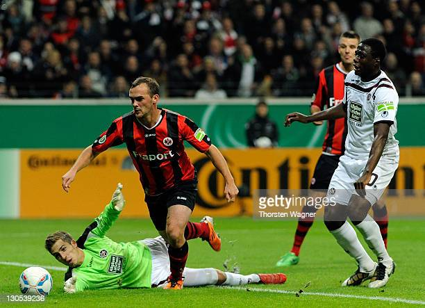 Erwin Hoffer of Frankfurt battles for the ball with Kevin Trapp of Kaiserslautern during the DFB Cup second round match between Eintracht Frankfurt...