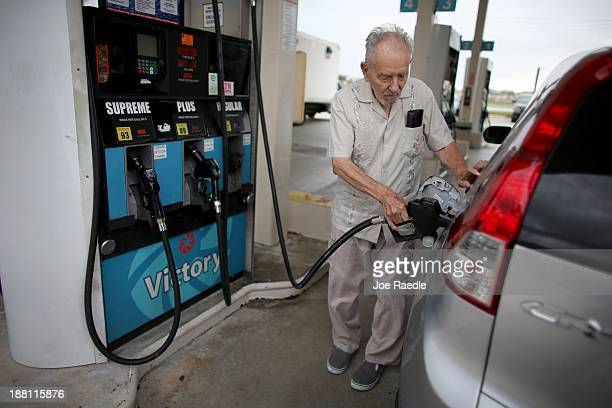 Erwin Kerr pumps gas into his car from a pump with a sign indicating the gas is containing up to 10 % ethanol at Victory gas station on November 15...