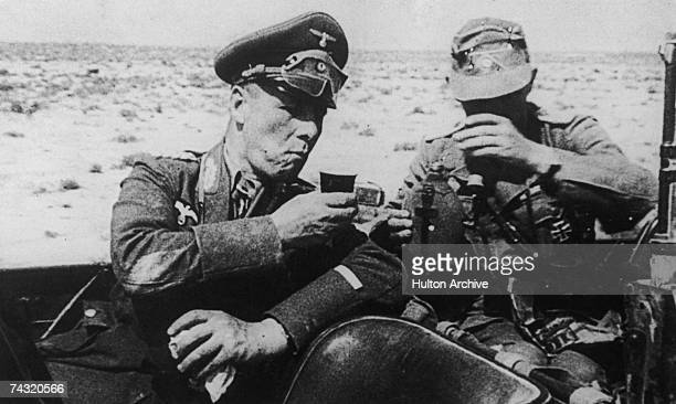 Erwin Rommel CommanderinChief of the German Africa Corps during World War II takes some refreshment during a tour of inspection in the Libyan desert...
