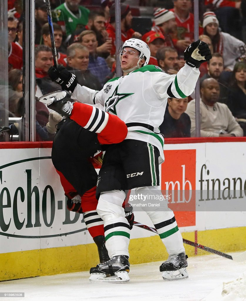 Esa Lindell #23 of the Dallas Stars collides with Patrick Sharp #10 of the Chicago Blackhawks along the boards at the United Center on February 8 2018 in Chicago, Illinois. The Stars defeated the Blackhawks 4-2.
