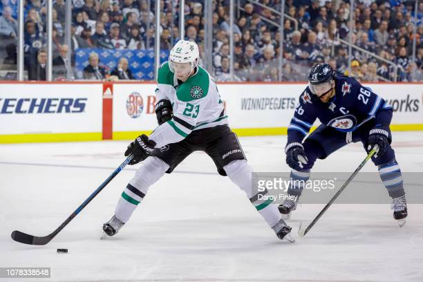 Esa Lindell of the Dallas Stars plays the puck down the ice as Blake Wheeler of the Winnipeg Jets gives chase during second period action at the Bell...