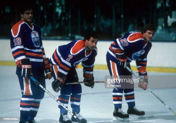 Esa Tikkanen Paul Coffey and Mike Krushelnyski of the Edmonton Oilers stand on the ice during pregame warmups before their game against the New York...