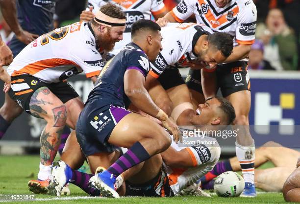 Esan Marsters of the Tigers is congratulated by Benji Marshall of the Tigers and his teammates after scoring a try during the round 10 NRL match...