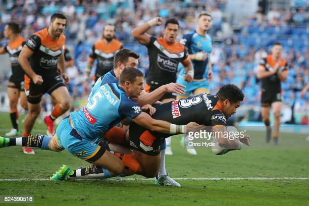 Esan Marsters of the Tigers scores a try during the round 21 NRL match between the Gold Coast Titans and the Wests Tigers at Cbus Super Stadium on...